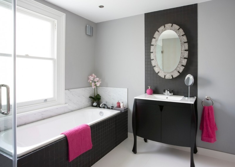 monochromatic walls idea black painted vanity with white marble countertop round decorative mirror with silver frames white bathtub with black ceramic walls