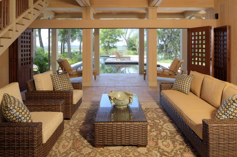 morning room furniture rattan sofa glass surface table carpet hardwood floor wooden doors chaise lounges limestone walls tropical design