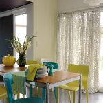 Mustard Yellow Wall Painting White Lace Window Curtain Lime Green & Peacock Blue Chairs Wood Top Dining Table
