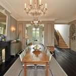 narrow dining room table chairs chandelier carpet dark floor stairs mirror traditional style