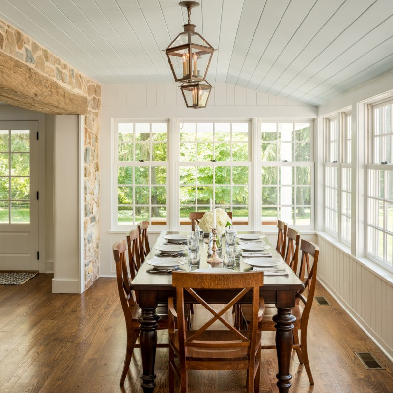narrow dining room tables hardwood floors tall back chairs multiple windows hanging lamps stone tiles white ceiling farmhouse design
