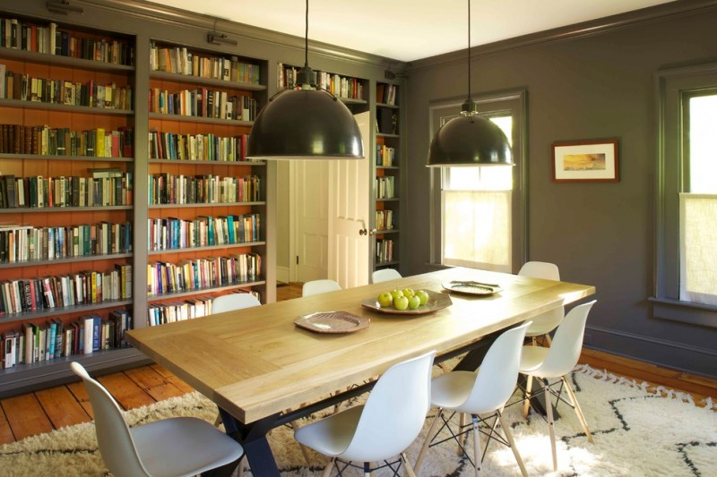 narrow dining room tables wall bookshelves hardwood floors black pendants fur carpet low back chairs windows farmhouse design