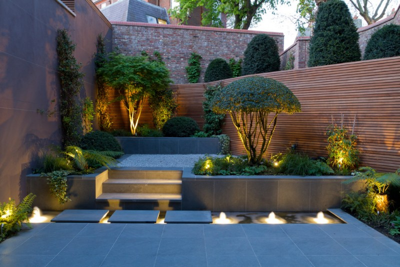 natural stone floating pavers of basalt stone fountain domed plant sculptures horizontal wood fence pebbels brick walls concrete tiles wall