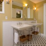 pedestal sink with backsplash tiles baskets storage wall lamps window blind traditional style