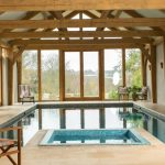 Pool Enclosure With Big Logs White Ceillings Concrete Walls Concrete Floors Black Wrought Iron Chairs Glass Windows And Doors With Wood Trims