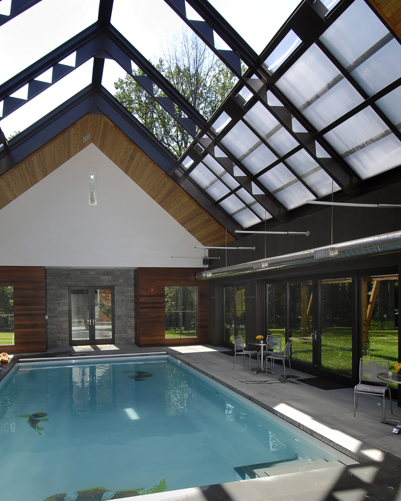 pool enclosure with retractable ceilings rectangular interior pool white tiles floors natural stones and dark toned wood walls glass windows and door
