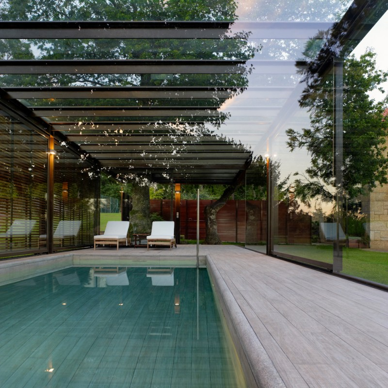 rectangular interior pool with glass enclosure white cedar wood floors a pair of exterior chairs