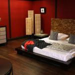 red walls wood flooring corner molding master bedroom unique headboard antique rattan lamps