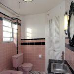 Retro Pink Bathroom Idea Pink Tiles And White Concrete Walls Accented By Black Lines One Piece Toilet In Pink Pink Bathtub Permanent Bathroom Vanity With Black Tiles Top And Stainless Steel Sink