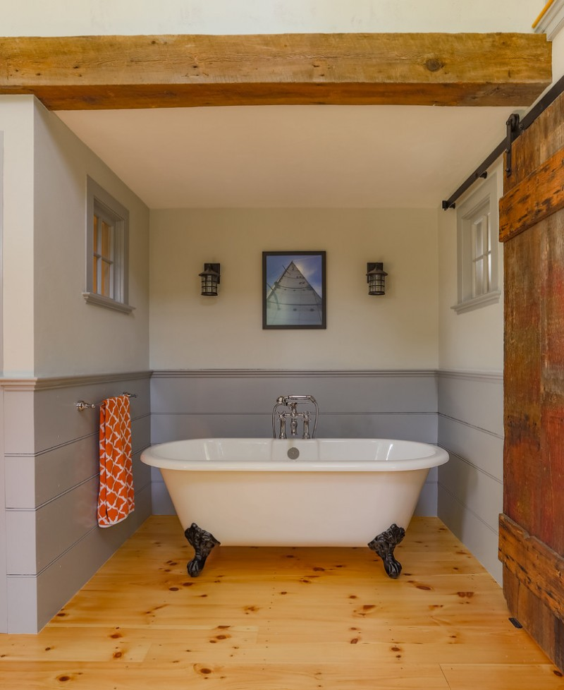 rustic farmhouse bathroom with claw foot bathtub wood floors sliding barn door interior windows grey walls white walls