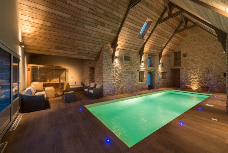 rustic interior pool with wood slabs enclosure natural stones walls wood slabs floorings glass sliding door