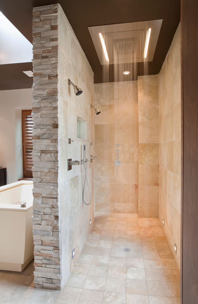shower area with limestone for flooring and wall, tiles for rain ceiling, two shower ficture on the wall