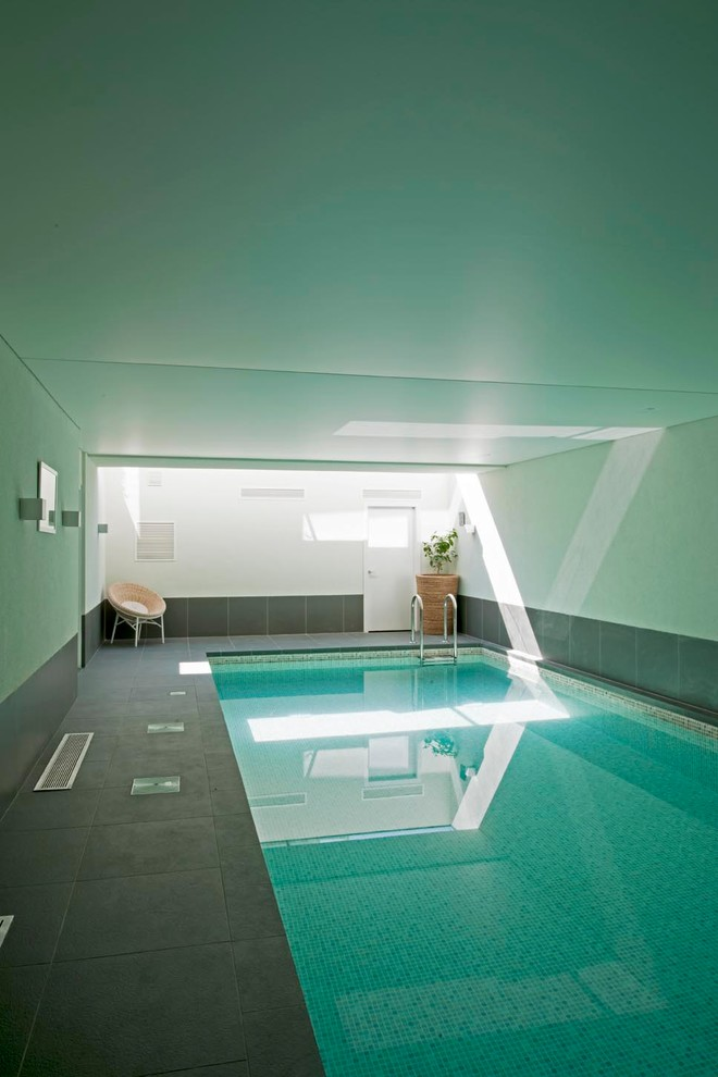 simple and minimalist interior pool with enclosure black ceramic floors white walls white ceiling a chair on corner