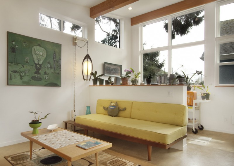 simple and modern living room with yellow couch lower & white room divider with wood top garnished by small vivid plants non finished wood center table area rug in light brown white walls idea