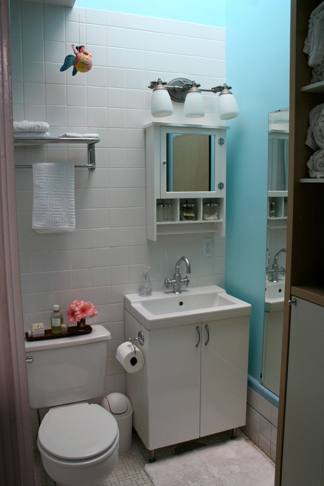 small but eclectic bathroom with white ceramic walls blue painted concrete walls two piece toilet in white square and white undermount sink with white cabinet wall mounted storage with mirror door