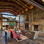 stone wall built in stone shelves wall mounted TV wooden beams stone floor floor to ceiling glass windows red sofa