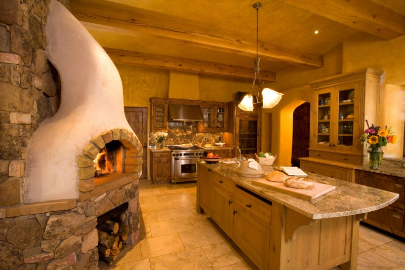 stone wall fireplace chimney log storage tiled floor kitchen island ceiling beams granite backsplash granite countertop archway
