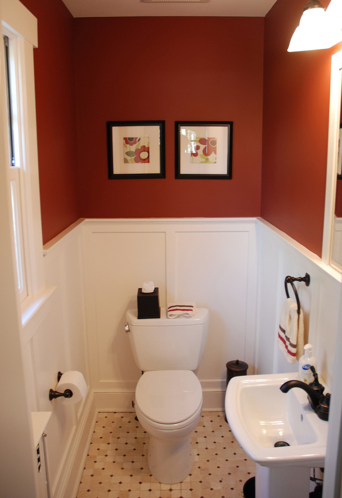 traditional bathroom deep red walls accented by clean white baseboard white toilet white pedestal sink white ceramic tiles with black accents two picture frames
