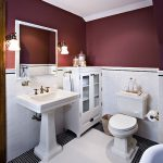 Traditional Bathroom Half Way Deep Red Walls Half Way White Ceramic Walls White Pedestal Sink Two Piece Toilet Cabinet White Framed Mirror Small White Ceramic Floors Accented By Black Ceramics