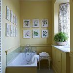 Traditional Bathroom Idea Light Yellow Walls Light Yellow Cabinets White Bathtub With Light Yellow Base White Toilet White Classic Vanity Chair Well Organized Picture Frames In White
