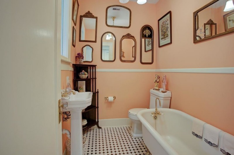 traditional bathroom idea with light orange walls decorative mirrors wall arts wood made crafts one piece toile in white claw foot bathtub in white white pedestal sink black and white ceramic floors