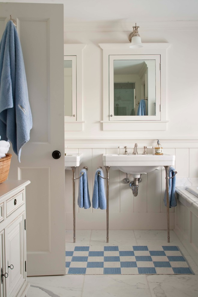 traditional bathroom with white vanity white concrete walls white subway tiles walls two wall mounted sinks two mirrors with hidden storage white ceramic floors with blue white shower mat