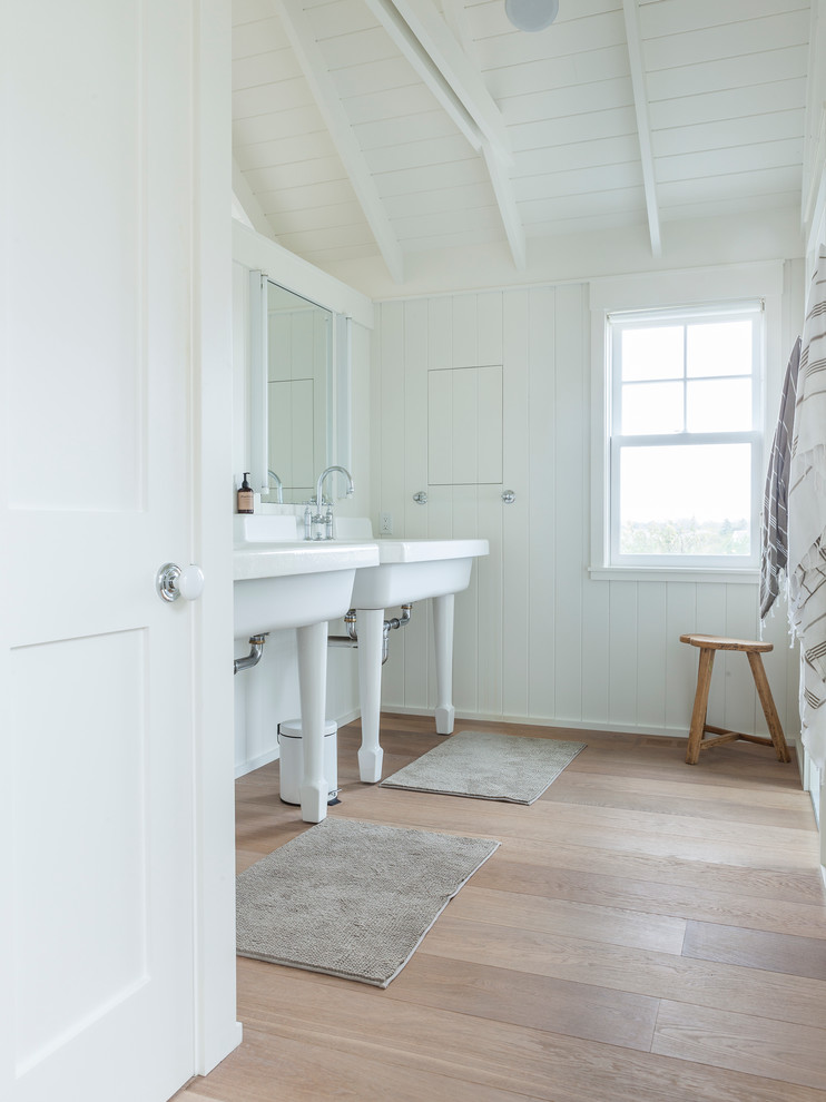 traditional bathroom with wood floors white finished wood walls white finishing ceilings two pedestal sinks small size wood bench