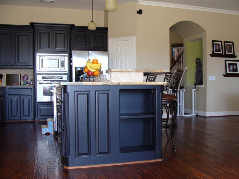 traditional kitchen with small wood top kitchen island with storage stainless steel appliances black iron chairs dark hardwood floors black painted kitchen cabinets