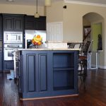Traditional Kitchen With Small Wood Top Kitchen Island With Storage Stainless Steel Appliances Black Wrought Iron Bar Chairs Dark Hardwood Floors Black Painted Kitchen Cabinets