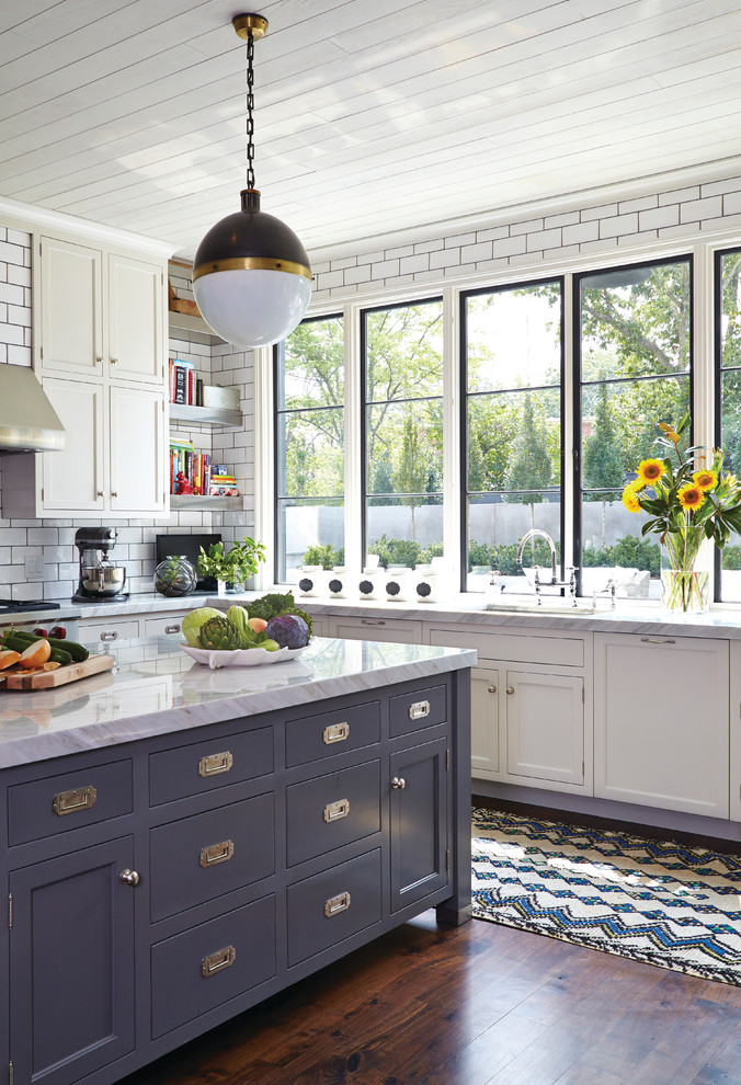 transitional kitchen design with white marble top kitchen island & storage L shape white countertop white cabinets white subway ceramic tiles backsplash dark hardwood floors kitchen mat with patterns