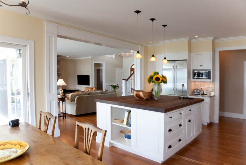 transitional kitchen idea with butcher block top kitchen island and white cabinets medium toned wood floors three pendant lamps