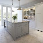 Transitional Kitchen Idea With Grey Kitchen Island With Granite Worktop And Storage White Marble Floors Clean White Kitchen Cabinets And Huge Storage Open Shelves Over Sink And Faucet