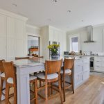 Transitional Kitchen Idea With Kitchen Island Extended To Dining Table Wood Chairs With Comforters I Shaped Countertop Floor To Ceiling Storage System In White Stainless Steel Appliances