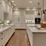 Transitional Kitchen Model Kitchen Island With White Cabinets Dominating White Granite Top And Electric Stove Medium Toned Wood Floors