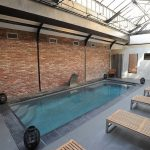 Transparent Glass Enclosure For Industrial Interior Pool Red Brick Walls Grey Tiles Floors Rectangular Pool Several Wood Benches Some Fountains
