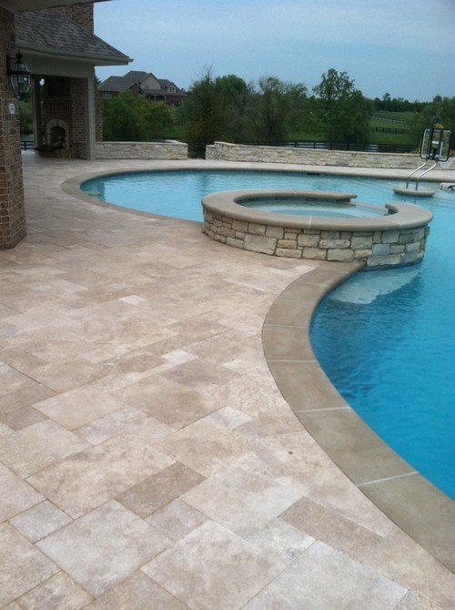 travertine pavers pool deck hanging lamp brick walls patio fireplace trees decorative plants traditional design
