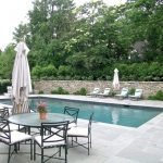 travertine pavers pool deck loungers low back chairs round table stone walls sunbrella trees traditional design