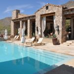 travertine pavers pool deck lounges sunbrella hanging lamps stone walls curtains decorative plants mediterranean design