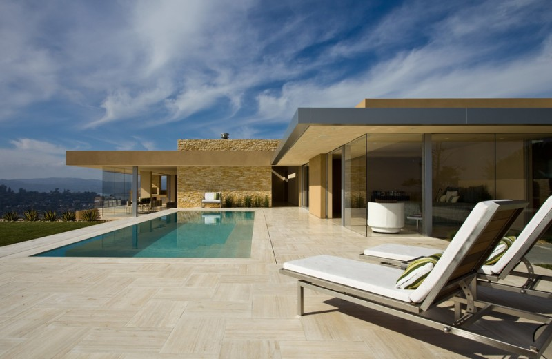 travertine pavers pool deck patio loungers throw pillows double glass doors oversized windows garden modern design