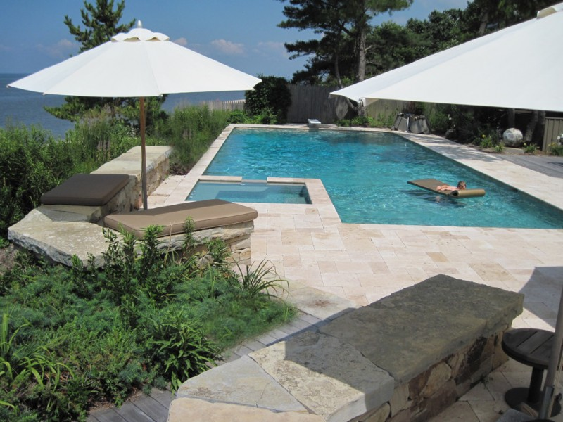 travertine pavers pool deck sunbrella mats wood stool stone blocks plants decorations contemporary design