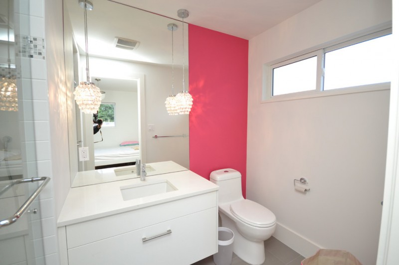 trendy and conteporary bathroom idea deep pink walls clean white walls white bathroom vanity with deep undermount sink white toilet a couple of crystal lamps