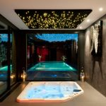 Trendy And Glamour Enclosed Whirl Pool Asymmetrical White Whirl Pool Frameless Glass Door And Windows Dark Ceramic Floors Dark Concrete Walls