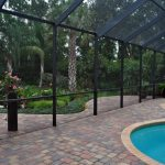 Tropical Interior Pool Supported By Transparent Enclosure With Black Aluminum Bars Paver Flooring Idea Curved Pool Idea
