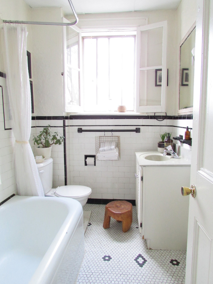 urban style bathroom in white white bathtub semi transparent shower curtain two piece toilet in white white bathroom vanity white undermount sink white subway ceramic walls white ceramic floors