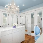 white cabinets medium tone hardwood floors beautiful light blue ceiling with crystal chandelier in walk in closet marble countertop dresser