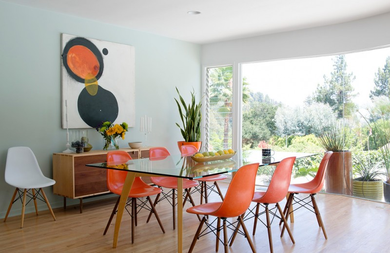 white orange chairs green walls and light hardwood floors glass table wall art work big glass window wooen cabinet