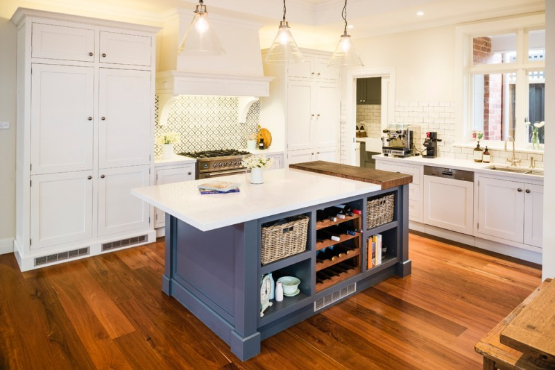 white top kitchen island with navy blue base and storage addition white kitchen idea with white cabinets white countertop stainless steel appliances white subway ceramic walls two white storage