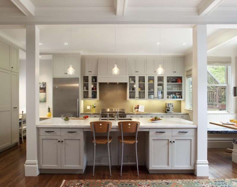 white traditional kitchen with white kitchen island with storage and wood chairs stainless steel appliances beige ceramic tiles backsplash white upper and lower cabinets dark wood floors