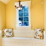 window seats with storage bright yellow wall bright wooden floor flowery pillow white storage