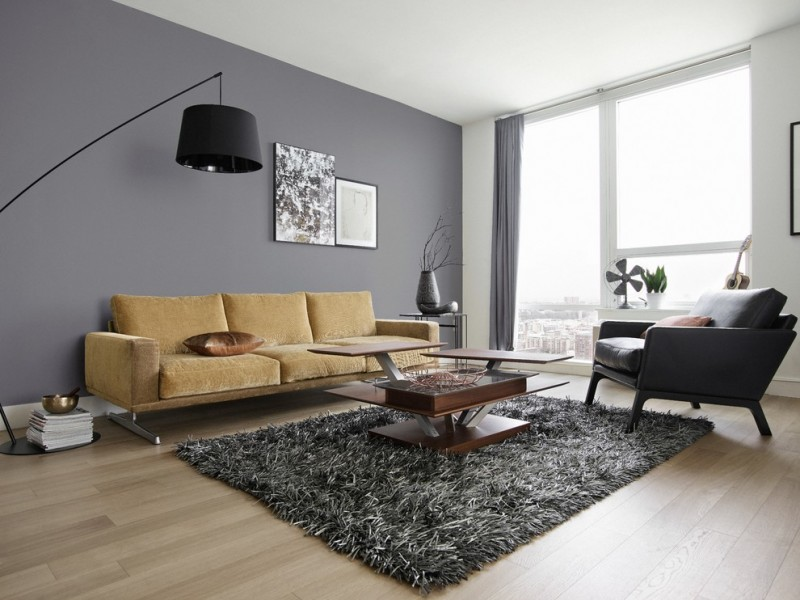 yellow couch black leather reading chair fluffy grey area rug dark hardwood center table in unique design pale toned wood floors grey wall painting modern standing lamp in black